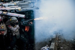 A police officer fires his teargas launcher during a clash with students protesting against a new law they say has crippled the country's anti-corruption agency