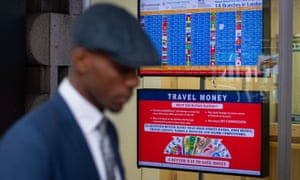 A man walks past a screen displaying foreign exchange rates