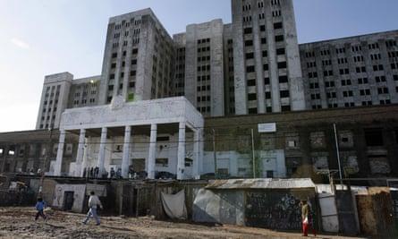 Hidden City residents walk past the 'White Elephant', along-abandoned building now undergoing careful demolition.