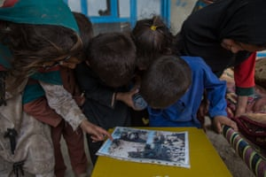 Children look over pictures of their destroyed house in Noorai village, a Taliban stronghold in Khost province. The family – including Mariam – now live in a rental house in Khost City.