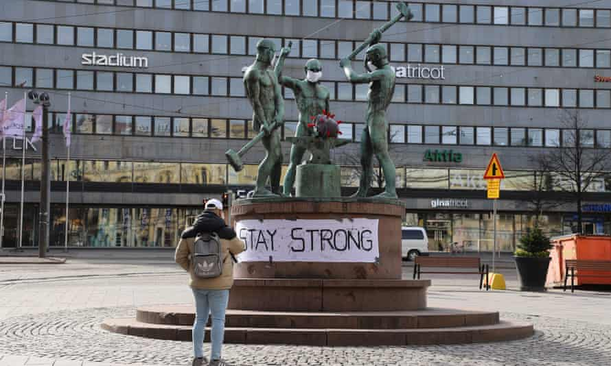 A man  takes a picture of the famous city sculpture Three Smiths, which have facial masks, in Helsinki, Finland