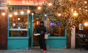 A masked takeaway driver leaving a restaurant with a food delivery