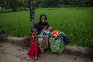 A Rohingya Muslim woman, Meenara Begum, who crossed over from Myanmar into Bangladesh, holds her son Sahid Noor and her daughter Rashida Begum as she sit on a roadside as her husband is waiting for food aid inside Balukhali refugee camp, Bangladesh
