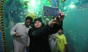 A woman takes a selfie inside the shrine
