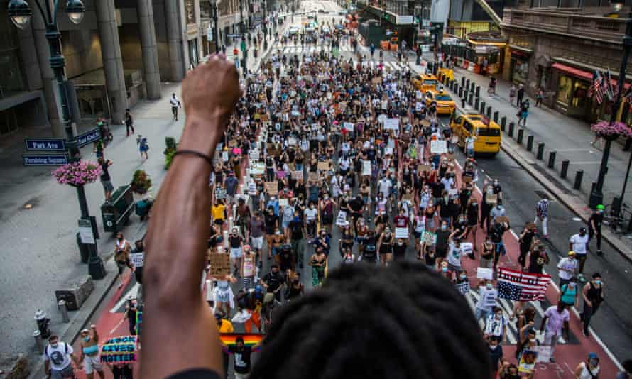 man raises arm in support as Black Lives Matter protesters walk in New York