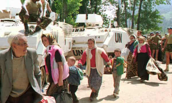 Muslim refugees from Srebrenica pass by UN armored personnel carriers, 13 July 1995.