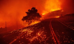 Embers blow across a road as wind rips through the area during the Kincade fire near Geyserville.