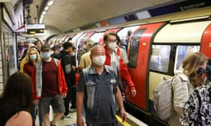 People wearing protective face masks walk along a platform on the London Underground.