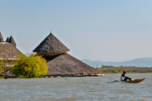 A fisherman paddles a traditional raft made from reeds past one of the submerged buildings of the Soi Lodge on the shores of Lake Baringo.