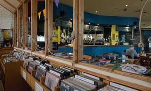 Interior of Mono, Glasgow. In the foreground are racks of music vinyl while in the background there is a cafe area.
