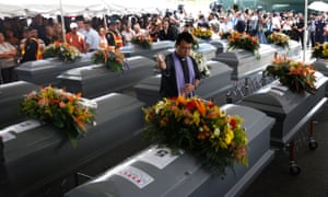 A priest blesses the coffins of 16 Hondurans, discovered with another 56 murdered migrants in a mass grave in San Fernando in 2010.