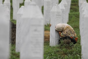 A relative of a Srebrenica genocide victim mourns by a gravestone at the Srebrenica Potocari memorial, ahead of the burial of recently-identified remains of 33 victims of the genocide.