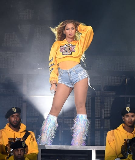 Beyonce in yellow hoodie, jean shorts and white-fringed go-go boots.