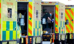 A paramedic wearing PPE prepares an ambulance at a hospital in east London