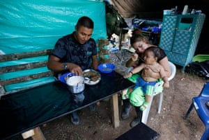 Farc rebel couple Jerly Suarez, right, and Vicente Pulecio eat lunch with their nine-month-old son within a demobilization zone in Putumayo state.