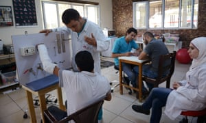 A Syrian patient works with staff to learn how to do simple tasks with his hand again at Mowasah Reconstructive Surgery hospital.