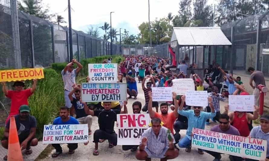 Refugees and asylum seekers hold up banners during a protest at the Manus Island immigration detention centre in Papua New Guinea