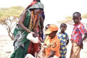 Dr Judy Kimaru helps to feed a goat kid in Yaa Gara, Marsabit County
