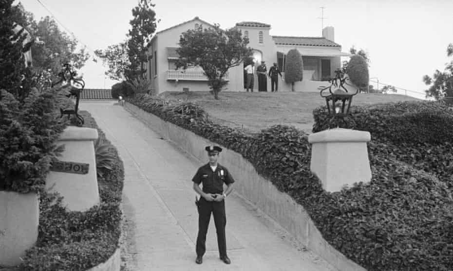 A police officer blocks the driveway while officers search the front of the house where Leno and Rosemary LaBianca were killed.