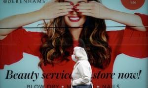 Woman in mask walks past advertisement