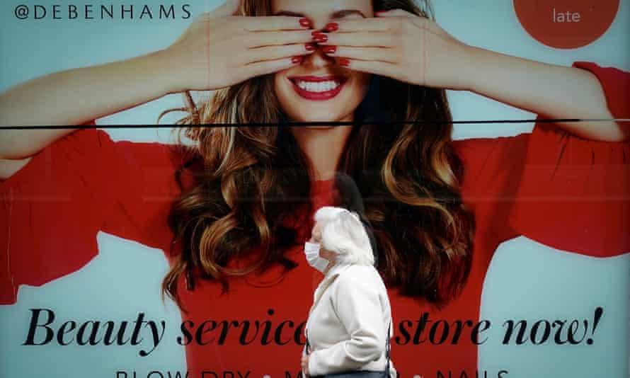 Elderly woman in mask walks past Debenhams shop front
