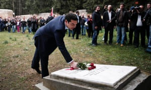 Alexis Tsipras leaves some flowers on a monument during a ceremony at the Kessariani shooting range site.