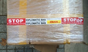 A box on pavement with tape indicating it was sent as a diplomatic bag