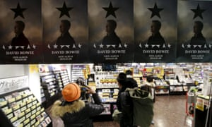 A Japanese fan takes a photo of posters for David Bowie's album Blackstar in a shop in Tokyo.