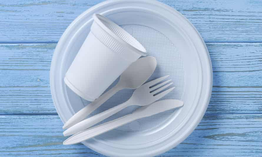 Disposable tableware and cutlery on blue wooden table, top view