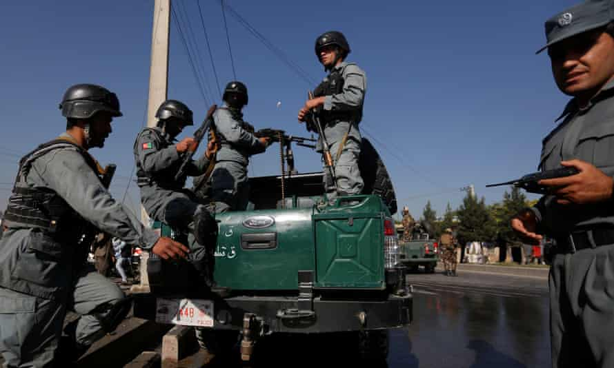 Afghan policemen arrive at the site of the suicide bombing.