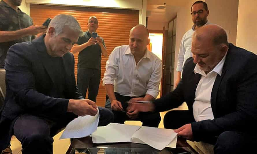 From left, Yair Lapid, Naftali Bennett and Mansour Abbas sign the coalition agreement that was reached on Wednesday.
