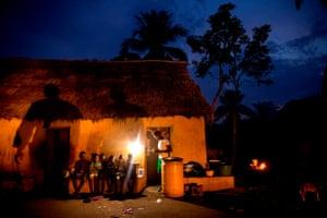 A teacher gives classes at night under a sun lamp in the village of Gbekandji, Benin