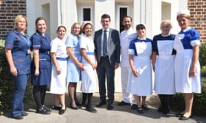 Andy Burnham, the mayor of Manchester, poses with nurses in uniforms to represent each decade of the NHS during a visit to Trafford hospital.