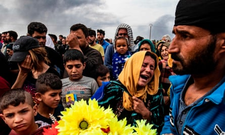 Mourners at the funeral of civilians and fighters, who died during attacks by Turkish-backed forces on the border town of Ras al-Ayn this week.
