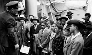 Jamaican immigrants are greeted by RAF officials from the Colonial Office after the ex-troopship HMT Empire Windrush docks at Tilbury.