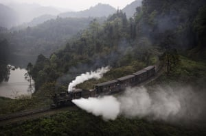 A coal powered steam train carrying tourist cars lets off steam near Bagou