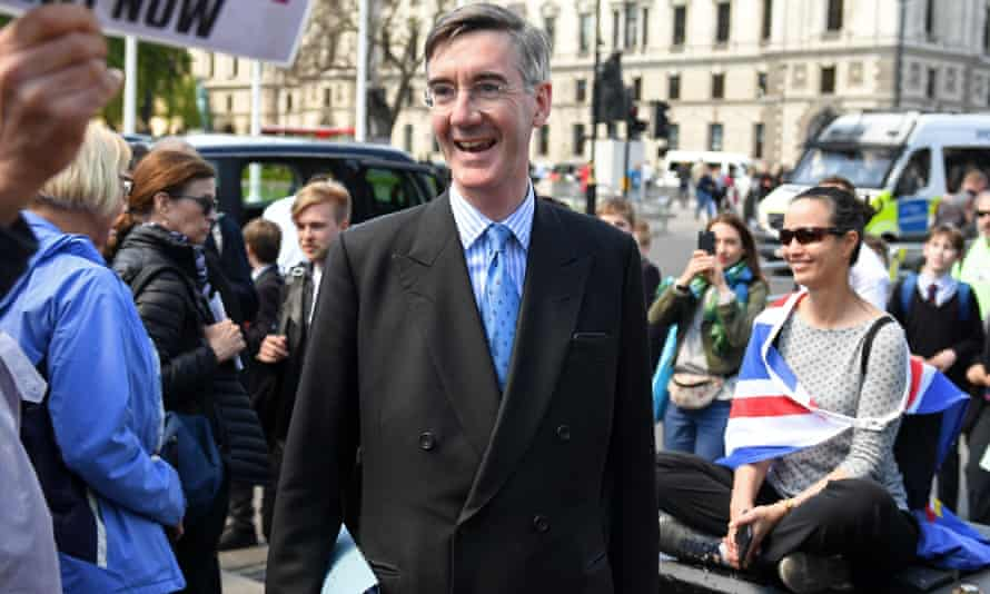 Jacob Rees-Mogg walks past anti-Brexit protesters outside the Palace of Westminster.