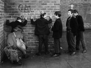 Belfast, Northern Ireland, 1972. Daily life goes on in the city, even with a constant military reminder of the anti-English struggle, as five boys dressed for carnival celebrations are frisked by a soldier against a wall