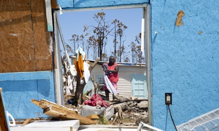 People dry clothes amid debris and rubble in Great Abaco, on 9 September.