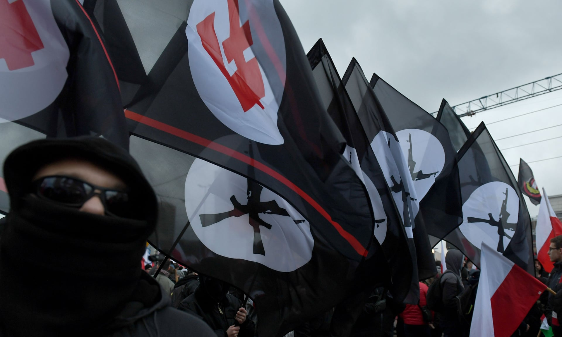 Far-right marchers brandish banners depicting a red falanga, a far-right symbol dating from the 1930s