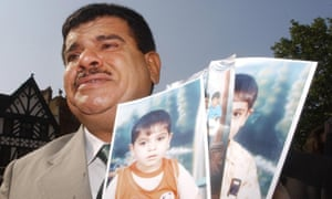 Daoud Mousa, father of Baha Mousa who was killed in British army custody in Basra in 2003, with photos of his grandchildren, 2004