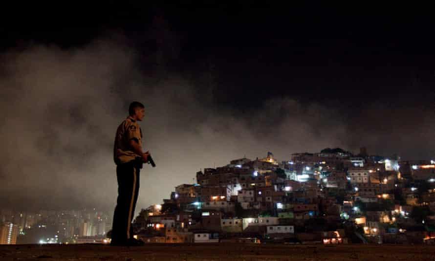A police officer patrols the slum district of Petare in Caracas, Venezuela