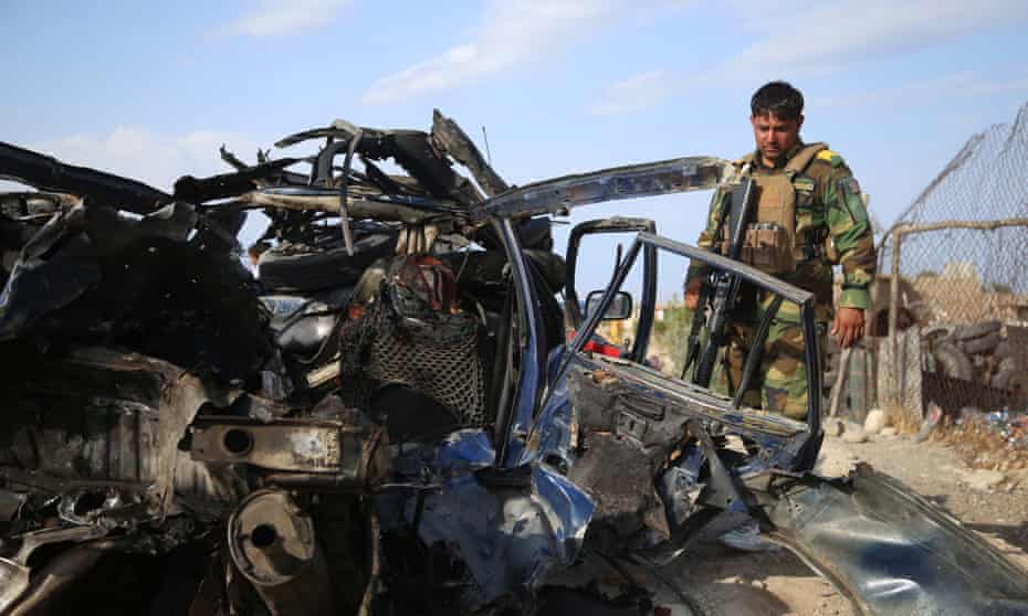 Afghan security officials inspect the scene of a road side bomb blast that killed six civilians on the outskirts of Jalalabad