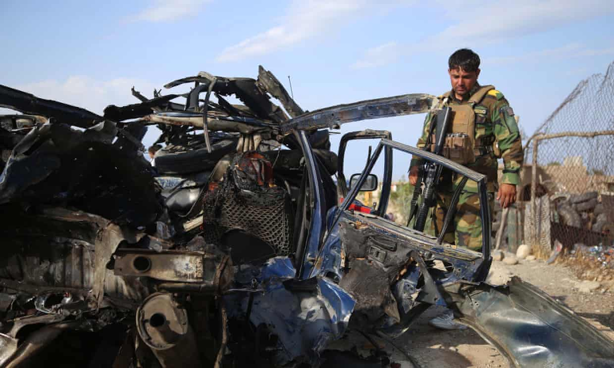 Afghan security officials inspect the scene of a road side bomb blast that killed six civilians on the outskirts of Jalalabad. Photograph: Ghulamullah Habibi/EPA