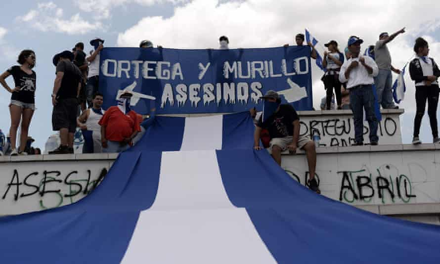 Anti-government demonstrators in Managua hold a banner reading 'Ortega and Murillo assassins', referring to the Nicaraguan president, Daniel Ortega, and the vice-president, his wife Rosario Murillo.