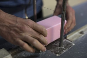A factory worker cuts soap into bars