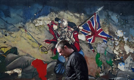A man walks past a mural marking unionist territory in Derry, Northern Ireland.