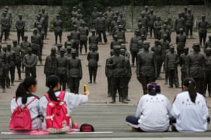 Students sit at the Chinese Heroes Statues Plaza, which displays war heroes from the War of Resistance against Japan