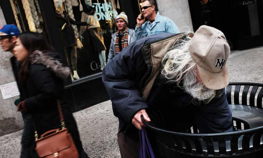 A homeless man looks for food in a litter bin on a retail street in New York.