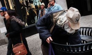 A man looks for food in a garbage can in New York City